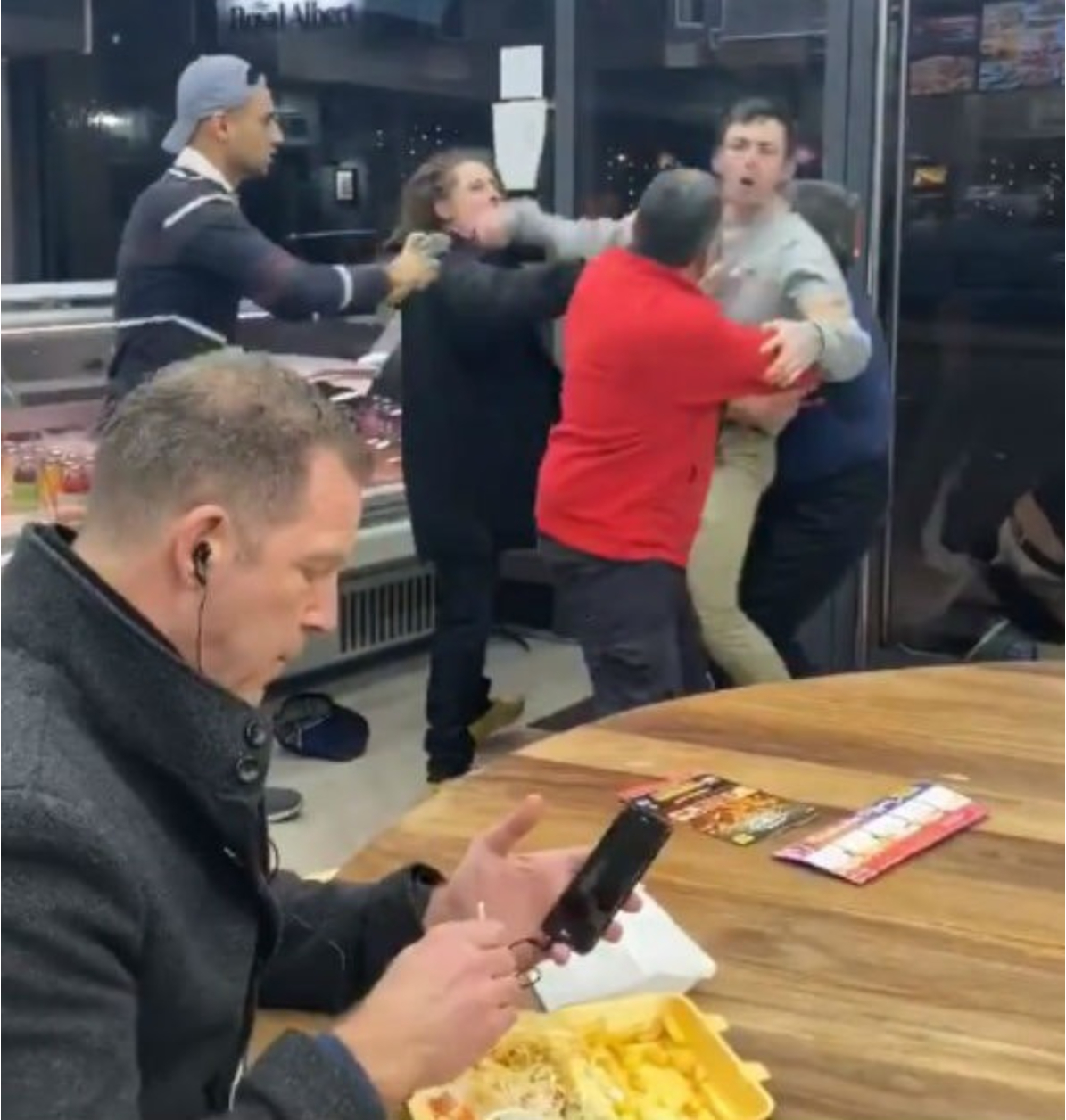 Man Calmly Eating Kebab in Shop During Fight Meme Template